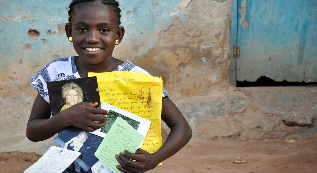 Work Hard At School: ìMy sponsor always tells me in her letters, to work hard at school. I am trying because I want to be a nurse in future,î Najat, nine-year old sponsored girl said smiling. Najat (age 9) has never met her sponsor but she knows how she looks like. She is one of the children in the Ashanti Area Development Program sponsorship program who often receives greeting cards, photographs, colored pencils, writing pad and photographs, among others, from her sponsor.Najat holding letters and photographs from her sponsor. Summary: Context: The occupation of the people is mainly farming. They leave very early for their farms where they plant maize, yam, groundnut, garden eggs and tomatoes. When they return in the evening, girls assist their mothers to prepare the evening meal. You can tell food is cooking from the smoke rising from firewood they use. SHARE assignment: s100591-2, photos and captions only. Project name: Ashanti-Gap ADP Funding: United States Africa digital color horizontal